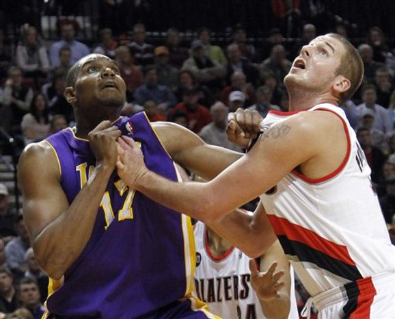 Los Angeles Lakers center Andrew Bynum left, and Portland Trail Blazers center Joel Przybilla work for position on a rebound during the first half of an NBA basketball game in Portland, Ore., Wednesday, Feb. 23, 2011. (AP Photo/Don Ryan)