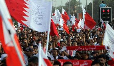 "Anti-government protesters march on Wednesday, Feb. 23, 2011, to welcome newly released political prisoners to Pearl Square in Manama, Bahrain. The banner at center reads, ""I love you, my country."" (AP Photo/Hasan Jamali)"