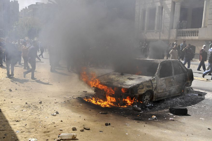 A fire set in a car believe to be set by hundreds of low-ranking police near the security headquarters in Cairo, Egypt, Wednesday, Feb.23, 2011, after four days of protests to demand better salaries. (AP Photo/Hossam Khalil)