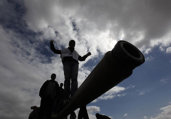Libyan citizens stand atop a destroyed armored vehicle at Al-Katiba military base, in Benghazi, Libya, Thursday Feb. 24, 2011. In cities across the east, residents rose up and overwhelmed government buildings and army bases, joined in many cases by local army units that defected. (AP Photo/Hussein Malla)