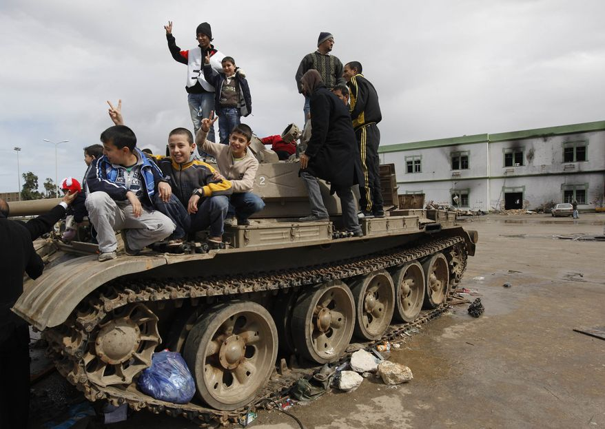 """Libyan boys flash """"V"""" signs Thursday while standing over a destroyed cannon tank at Al-Katiba military base in Benghazi, Libya. The base was overtaken days earlier by anti-Gadhafi protesters. (Associated Press)"""