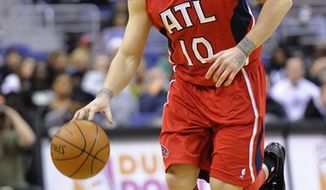 In this Feb. 5, 2011, photo, Atlanta Hawks guard Mike Bibby dribbles the ball against the Washington Wizards during an NBA basketball game in Washington. The Hawks were finalizing a deal to acquire guard Kirk Hinrich from the Washington Wizards, upgrading the Atlanta backcourt for the playoff run, a person familiar with the decision told The Associated Press on Wednesday. The person said that Bibby is among several players involved in the trade. (AP Photo/Nick Wass)