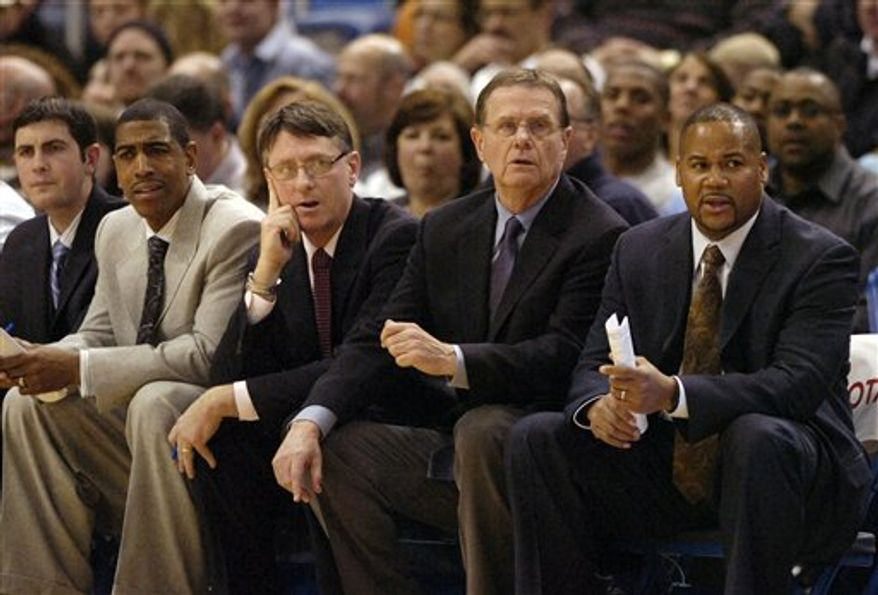 Members of Connecticut's coaching staff watch during the first half of the team's NCAA college basketball game against Marquette in Hartford, Conn., on Thursday, Feb. 24, 2011. Coach Jim Calhoun was not able to attend the game because of a family funeral. (AP Photo/Fred Beckham)