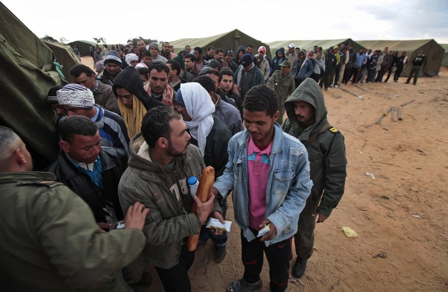 Egyptians, who used to work in Libya, and fled the unrest in the country wait for their breakfast in a makeshift refugee camp set up by the Tunisian army, at the Tunisia-Libyan border, in Ras Ajdir, Tunisia, Friday, Feb. 25, 2011. (AP Photo/Lefteris Pitarakis)