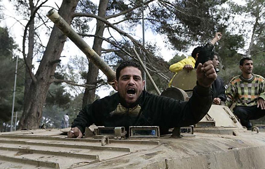 In this photo released by China's Xinhua News Agency, an anti-government protester celebrates on an army tank in the east Libyan city of Albayda Thursday, Feb. 24, 2011. (AP Photo/Xinhua, Nasser Nouri)