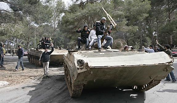 In this photo released by China's Xinhua News Agency, anti-government protesters celebrate on army tanks in the east Libyan city of Albayda Thursday, Feb. 24, 2011. (AP Photo/Xinhua, Nasser Nouri)