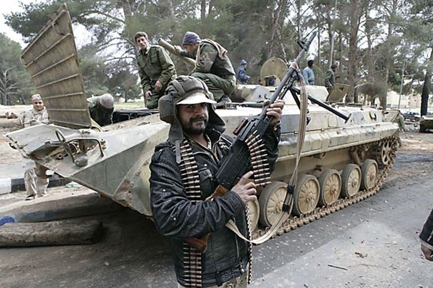 In this photo released by China's Xinhua News Agency, a man holding an automatic machine gun poses in front of a tank in the east Libyan city of Albayda Thursday, Feb. 24, 2011. (AP Photo/Xinhua, Nasser Nouri)