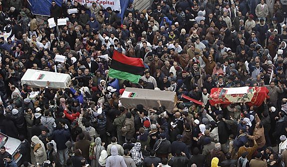Anti-Libyan leader Moammar Ghadafi protesters carry the coffin of protesters who were killed last week during the demonstrations, in Benghazi, Libya, on Friday Feb. 25, 2011.  Militias loyal to Col. Gadhafi opened fire on protesters streaming out of mosques in the Libyan capital on Friday, demanding the regime change, witnesses said, reporting at least four killed. Across rebellious cities in the east, tens of thousands held rallies in support of the first Tripoli protests in days. (AP Photo/Hussein Malla)(AP Photo/Hussein Malla)