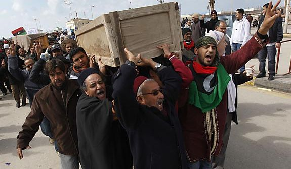 Mourners carry the coffins of two protesters who were killed last week during the demonstrations against Libyan leader Moammar Ghadafi in Benghazi, Libya, on Friday Feb. 25, 2011. Militias loyal to Col. Gadhafi opened fire on protesters streaming out of mosques in the Libyan capital on Friday, demanding the regime's ouster, witnesses said, reporting at least four killed. Across rebellious cities in the east, tens of thousands held rallies in support of the first Tripoli protests in days. (AP Photo/Hussein Malla)