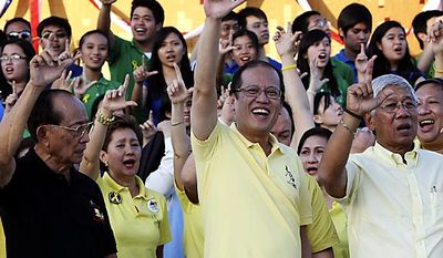 """Philippine President Benigno Aquino III, center, former President Fidel Ramos, left, and Defense Chief Voltaire Gazmin, flash the """"L"""" sign (for Laban which means Fight!) during the celebration of the 25th anniversary of the  People Power revolution Friday Feb. 25, 2011 at the People Power Monument along EDSA highway at suburban Quezon city northeast of Manila, Philippines. The nearly bloodless four-day people power revolution 25 years ago saw the ouster of the late strongman Ferdinand Marcos from 20-year rule and helped install current President Benigno Aquino III's mother Corazon """"Cory"""" Aquino to the presidency. (AP Photo/Bullit Marquez)"""