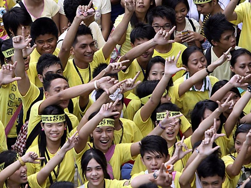 """Students flash the """"L"""" sign for Laban or Fight as they join the march celebrating the 25th anniversary of People Power revolution Friday, Feb. 25, 2011, in suburban Pasig City east of Manila, Philippines. The nearly bloodless four-day people power revolution 25 years ago saw the ouster of the late strongman Ferdinand Marcos from 20-year rule and helped install now President Benigno Aquino III's mother Corazon """"Cory"""" Aquino to the presidency.(AP Photo/Pat Roque)"""