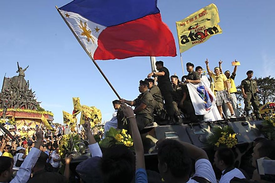 """Philippine soldiers and civilians mount an armored personnel carrier as they re-enact the support provided by tens of thousands of civilians to mutinous soldiers in the celebration of the 25th anniversary of the People Power revolution Friday Feb. 25, 2011, at the People Power Monument along EDSA highway at suburban Quezon city northeast of Manila, Philippines. The nearly bloodless four-day people power revolution 25 years ago saw the ouster of the late strongman Ferdinand Marcos from 20-year rule and helped install current President Benigno Aquino III's mother Corazon """"Cory"""" Aquino to the presidency. (AP Photo/Bullit Marquez)"""