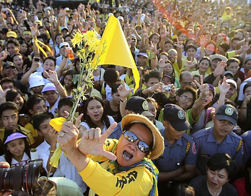 """Civilians flash an """"L"""" sign (for Laban which means Fight!) as they sing patriotic song during the celebration of the 25th anniversary of the People Power revolution Friday, Feb. 25, 2011, at the People Power Monument along EDSA highway at suburban Quezon city, northeast of Manila, Philippines. The nearly bloodless four-day people power revolution 25 years ago saw the ouster of the late strongman Ferdinand Marcos from 20-year rule and helped install current President Benigno Aquino III's mother Corazon """"Cory"""" Aquino to the presidency. (AP Photo/Bullit Marquez)"""