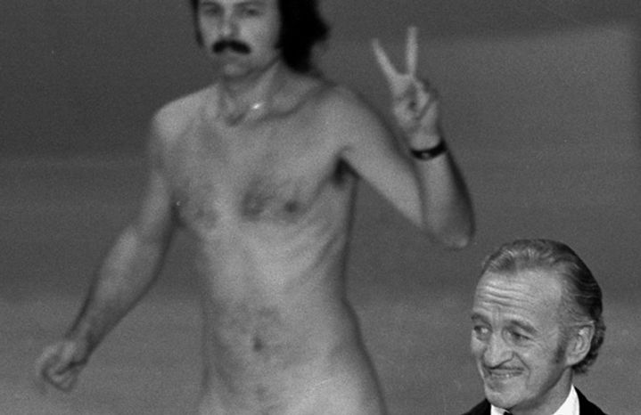 Actor David Niven presents an award as streaker Robert Ope crosses the stage during the 1974 Academy Awards show in Los Angeles. (
