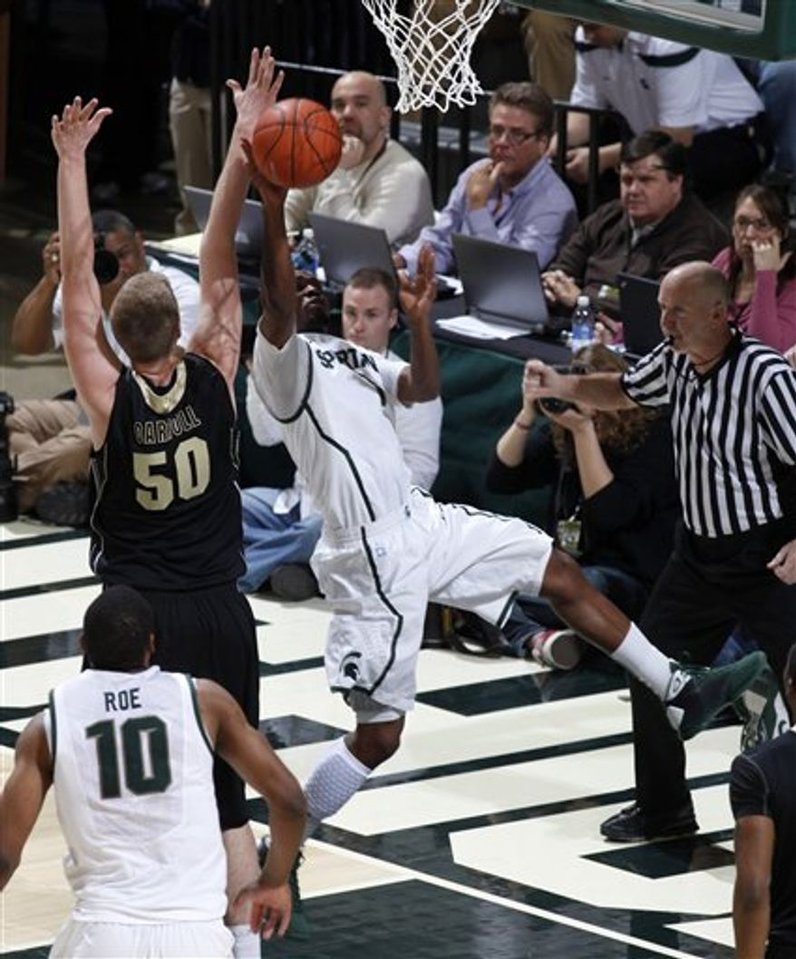 Michigan State's Kalin Lucas, center, shoots and draws a foul against Purdue's Travis Carroll (50) during the first half of an NCAA college basketball game, Sunday, Feb. 27, 2011, in East Lansing, Mich. (AP Photo/Al Goldis)
