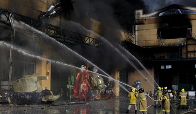 ** FILE ** Firefighters in Rio de Janeiro's Samba City work on Monday, Feb. 7, 2011, to put out a fire at warehouses where the city's samba groups store props and costumes for Brazil's largest Carnival parade. No injured were reported. (AP Photo/Felipe Dana, File)