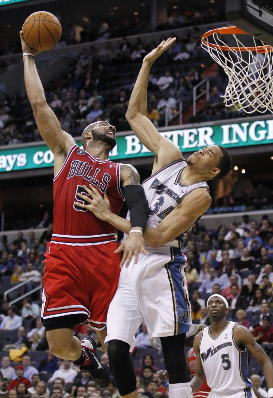 Chicago Bulls' Carlos Boozer (5) scores against Washington Wizards' JaVale McGee (34) during the first half of an NBA basketball game in Washington, Monday, Feb. 28, 2011. (AP Photo/Manuel Balce Ceneta)