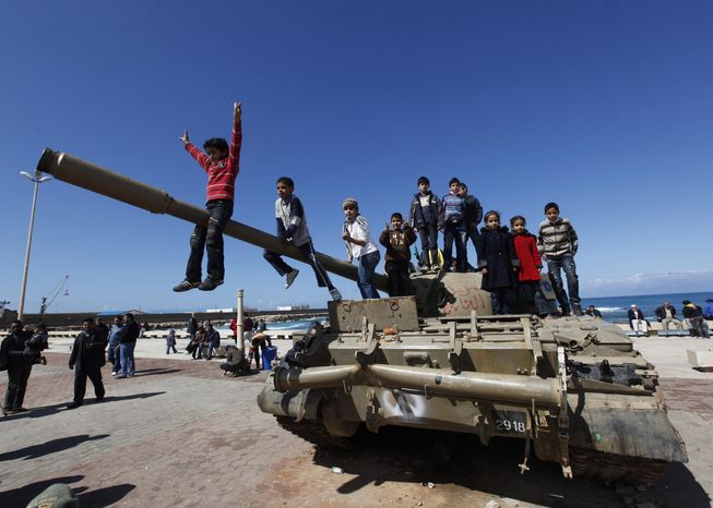"""A Libyan boy flashing a """"V"""" sign sits on the barrel of a destroyed army tank as he and other youths celebrate the freedom of the Libyan city of Benghazi on Monday, Feb. 28, 2011. The United States pressed its European allies on Monday to set tough sanctions on the Libyan government, while doubts emerged about the feasibility of a proposed no-fly zone to prevent Moammar Gadhafi's regime from launching aerial attacks against protesters. (AP Photo/Hussein Malla)"""
