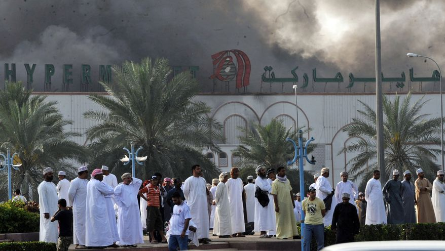 Omanis watch smoke rise from the Lulu hypermarket in Sohar, Oman, on Monday, Feb. 28, 2011. Omani security forces have blocked roads to Sohar, about 120 miles northwest of the capital of Muscat, after deadly clashes between pro-democracy protesters and riot police. (AP Photo)