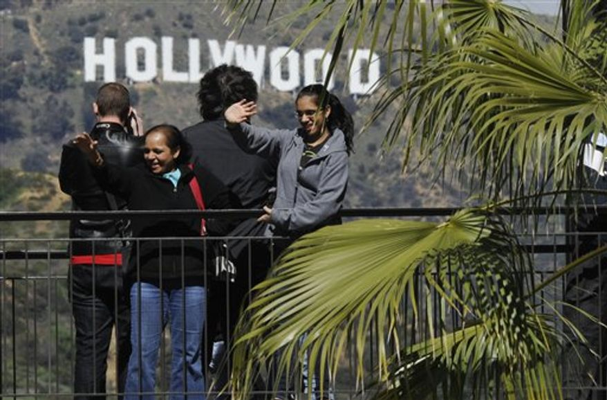 Fans wave on a balcony outside the Kodak Theatre in the Hollywood section of Los Angeles, Saturday, Feb. 26, 2011. The Kodak Theatre is the site of the 83rd Academy Awards which airs Sunday. (AP Photo/Mark J. Terrill)