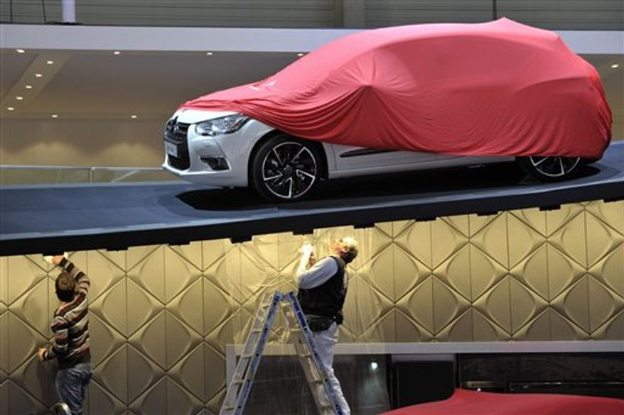 Representatives of the Fiat  booth stand  next to a car during the last preparations prior to the opening of the press preview days at the 81st Geneva International Motor Show in Geneva, Switzerland, Sunday, Feb. 27, 2011. The Motor Show will open its gates to the public March 3-13 presenting more than 260 exhibitors and more than 175 world and European premieres. (AP Photo/Keystone/Martial Trezzini)