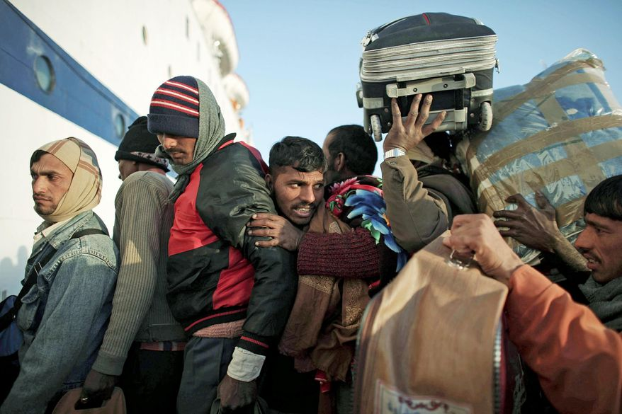 "Indian workers attempt to get on a ship leaving for Alexandria, Egypt, from the eastern city of Benghazi, Libya, on Tuesday. U.S. Secretary of State Hillary Rodham Clinton says the flow of refugees into Egypt and Tunisia is putting ""tremendous burdens"" on the two countries. (Associated Press)"