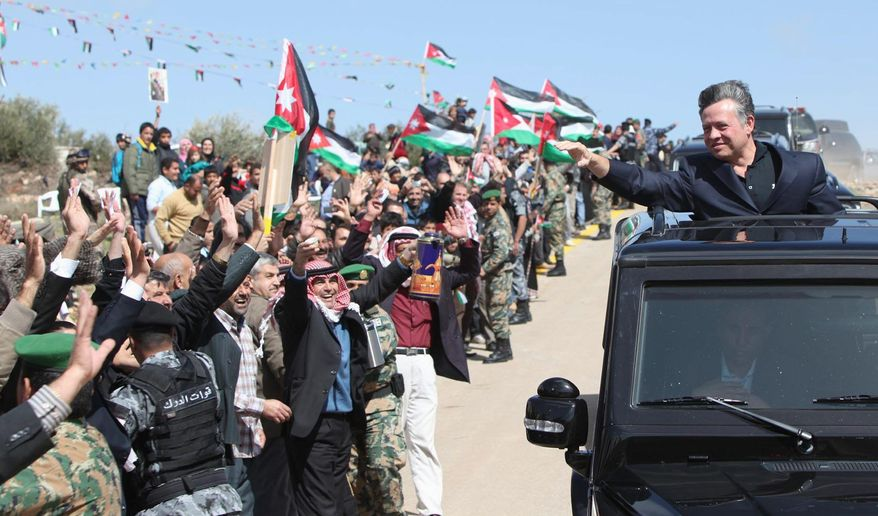 Jordan's King Abdullah II, in an image made available by the Jordanian Royal Court, waves to crowds who throng the streets of Mazar Shamali, 80 miles north of Amman, to greet the monarch on Tuesday. The king appears to be almost universally popular in Jordan. (Associated Press)