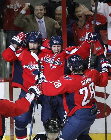 Washington Capitals' Brooks Laich, center, celebrates his goal with teammates Jason Arnott, left, and Alexander Semin (28), of Russia, late in the third period of an NHL hockey game against the New York Islanders in Washington, Tuesday, March 1, 2011. The Capitals won 2-1 in overtime. (AP Photo/Manuel Balce Ceneta)