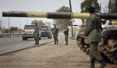 Soldiers and dozens of tanks from the Libyan military's elite Khamis Brigade, led by Moammar Gadhafi's youngest son Khamis Gadhafi, take positions and check vehicles after arriving hours earlier on the road in Harshan, 6 miles east of Zawiya, in Libya, Monday, Feb. 28, 2011. (AP Photo/Ben Curtis)