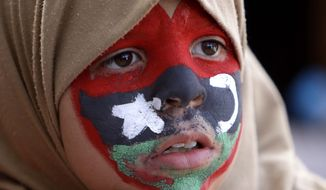 A young anti-Gadhafi protester with her face painted in the colors of the old Libyan flag during a protest at the court square, in Benghazi, Libya, on Tuesday March 1, 2011. (AP Photo/Hussein Malla)