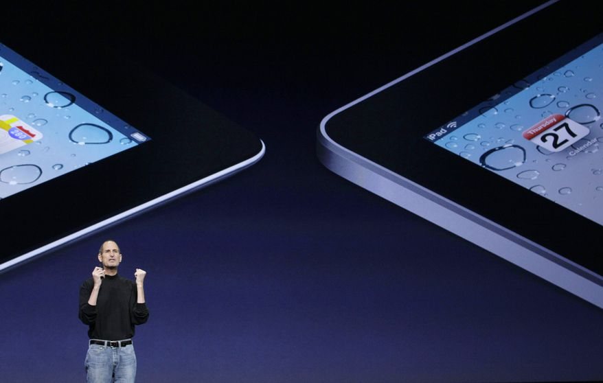 Apple Inc. Chairman and CEO Steve Jobs stands under images of the iPad 2, left, and the iPad at an Apple event at the Yerba Buena Center for the Arts Theater in San Francisco, Wednesday, March 2, 2011. (AP Photo/Jeff Chiu)
