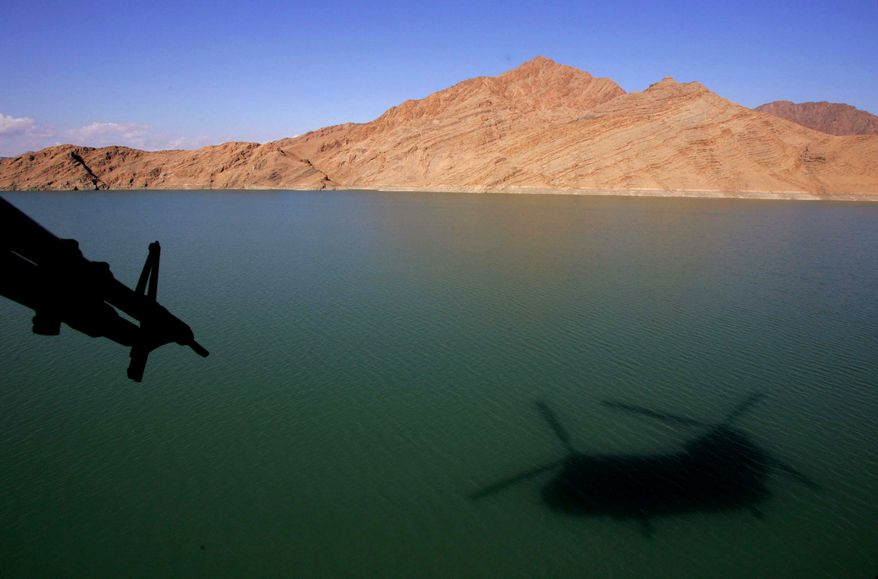 ** FILE ** The shadow of a British Royal Air Force Chinook helicopter is seen on the Kajaki reservoir as the chopper carries supplies to the forward operating base at Kajaki, in southern Afghanistan. (AP Photo/Manish Swarup)