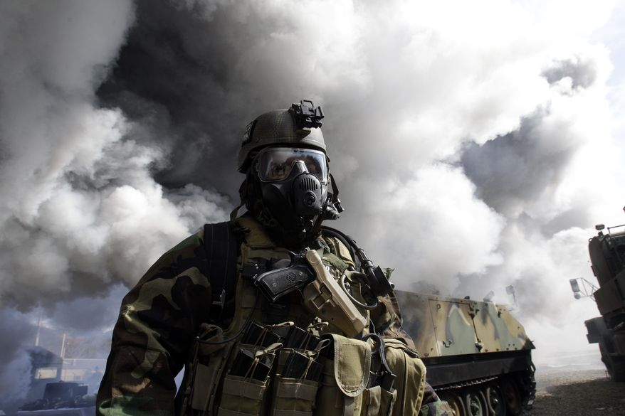 A U.S. soldier from the 2nd Infantry Division wears a gas mask and anti-chemical gear during a joint U.S.-South Korea military drill for chemical, biological, radiological and nuclear detection and response capabilities at Camp Casey in Dongducheon, South Korea, north of Seoul, on Thursday, March 3, 2011. Troops from the two allies kicked off their annual drills Monday, while North Korea slammed the maneuvers as a rehearsal for an invasion of the North that could trigger a nuclear war on the divided peninsula. (AP Photo/Lee Jin-man)