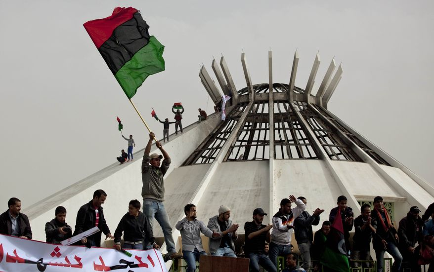 """Libyan protesters wave a national flag during a demonstration against Libyan leader Moammar Gadhafi, with the Green Book Centre building in background, in Benghazi, eastern Libya, Wednesday, March 2, 2011. Sign left reads """"Glory for the martyrs."""" (AP Photo/Kevin Frayer)"""
