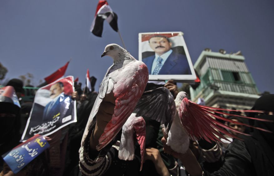 Female supporters of Yemeni President Ali Abdullah Saleh hold pigeons painted with the colors of their national flag during a rally in support of Mr. Saleh in Sanaa, Yemen, on Thursday, March 3, 2011. (AP Photo/Muhammed Muheisen)