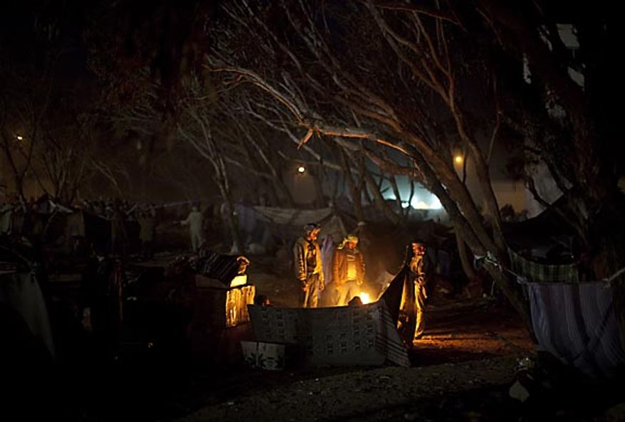 Men who used to work in Libya but recently fled the unrest, warm themselves up by a fire as they wait at the Tunisia-Libyan border, in Ras Ajdir, Tunisia,  Thursday, March 3, 2011.  (AP Photo/Emilio Morenatti)