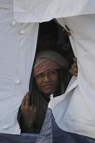A displaced man looks out from his tent in a refugee camp for people fleeing from unrest in Libya, at the Tunisia-Libyan border, in Ras Ajdir, Tunisia, Thursday March 3, 2011.  The camp was built to handle the large numbers of people crossing the border from Libya, and currently houses about 5,000 people, arriving in Tunisia carrying all their belongings. (AP Photo/Lefteris Pitarakis)