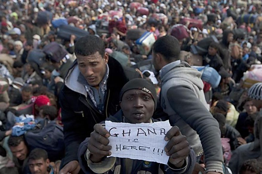 "A resident of Ghana displays a piece of paper mentioning his nationality as he waits with other refugees to enter Tunisia after fleeing Libya on the Libya-Tunisia border in Ras Ajdir, Tunisia, Tuesday, March 1 , 2011.U.N. refugee agency spokeswoman Melissa Fleming said Tuesday ""the situation is reaching crisis point"" at the Libya-Tunisia border where authorities say up to 75,000 people have fled Libya since Feb. 20. (AP Photo/Giorgos Moutafis)"