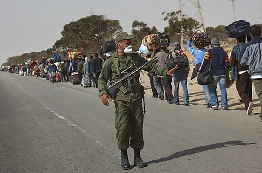 A soldier from the Tunisia army gestures, as men from Bangladesh, who used to work in Libya but recently fled the unrest, walk with their belongings alongside a road, as they head to a refugee camp after crossing the Tunisia-Libyan border, in Ras Ajdir, Tunisia, Friday, March 4, 2011.  Bangladeshis were angry at their country's government for not doing more to get the refugees home Most of the Bangladeshis appear to have arrived in Tunisia penniless because their Libyan employers did not pay them or because they were robbed on the way.(AP Photo/Emilio Morenatti)