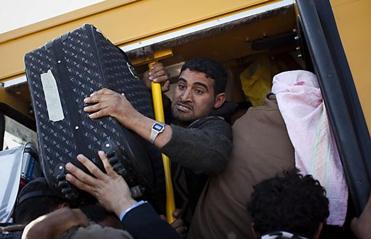 Egyptians who worked in Libya and are fleeing the unrest in the country pack a bus as they leave outside the Tunisia-Libyan border, in Ras Ajdir, Tunisia, Thursday, March 3, 2011. (AP Photo/Emilio Morenatti)