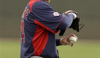 In this photo made Feb. 26, 2011, Cleveland Indians outfielder Grady Sizemore throws with a trainer during baseball spring training in Goodyear, Ariz. Attempting to come back from microfracture surgery on his left knee, Sizemore will probably not be ready for opening day and there's a chance he may never be the same. (AP Photo/Mark Duncan)