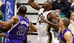 Utah Jazz forward Paul Millsap (24) works to tip a rebound while being guarded by Sacramento Kings center Marcus Thornton (23) and Kings guard Francisco Garcia (32) during the first half of their NBA basketball game in Salt Lake City, Saturday, March 5, 2011. (AP Photo/Steve C. Wilson)