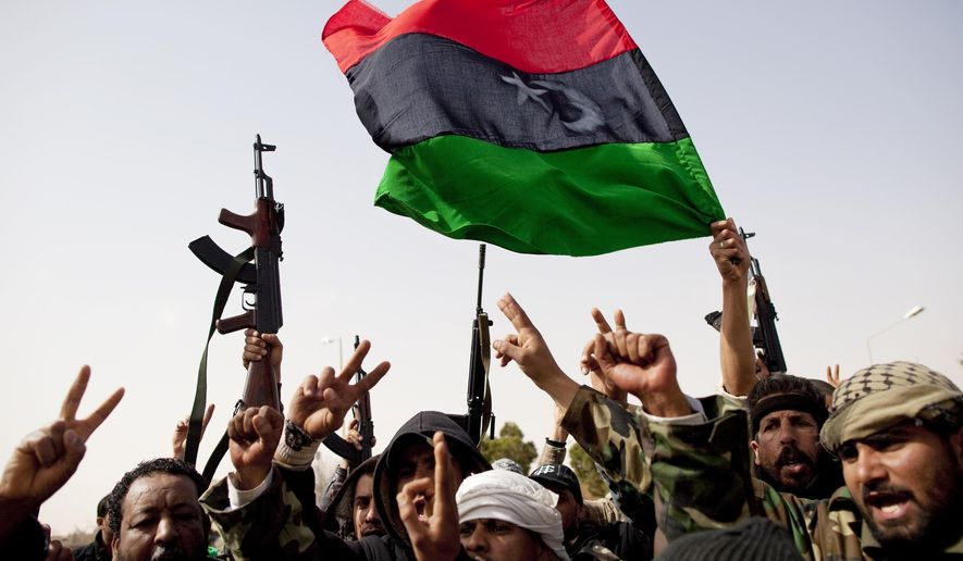 Libyan rebels who are part of the forces against Libyan leader Moammar Gadhafi hold a pre-Gadhafi flag as they celebrate after fighting against troops loyal to Gadhafi and capturing the oil town of Ras Lanuf, eastern Libya, Saturday, March 5, 2011. (AP Photo/Kevin Frayer)