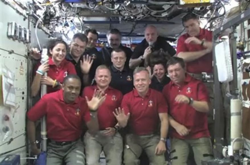In this image taken from video released by NASA, all twelve Discovery and International Space Station crew members wave during a call from President Barack Obama Thursday, March 3, 2011. From top left, Nicole Stott, Paolo Nespoli, Oleg Skripochka, Alexander Kaleri, Dmitry Kondratyev, commander Scott Kelly, Catherine Coleman, and Steve Bowen; from bottom left, Alvin Drew, pilot Eric Boe, commander Steve Lindsey, and Michael Barratt. (AP Photo/NASA)