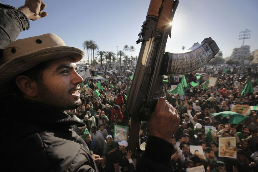Pro-Gadhafi soldiers and supporters waving flags and firing their guns in the air pour into Green Square in Tripoli, Libya, on Sunday, March 6, 2011, to celebrate claims of overnight military successes. (AP Photo/Ben Curtis)