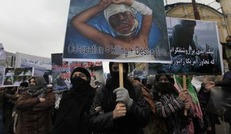 Female supporters of a left-wing political party hold placards carrying pictures of Afghans killed or wounded in recent air strikes during a protest in Kabul, Afghanistan, on Sunday, March 6, 2011. Hundreds of people marched through the streets of central Kabul to protest U.S. military operations and demand the withdrawal of foreign troops. (AP Photo/Dar Yasin)