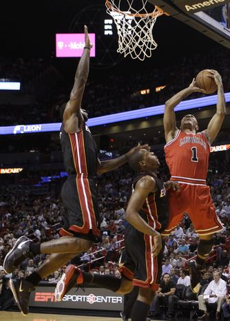 Chicago Bulls' Derrick Rose (1) shoots as Miami Heat's LeBron James, left, and Mario Chalmers, center, defend in the first quarter of an NBA basketball game in Miami, Sunday, March 6, 2011. (AP Photo/Lynne Sladky)