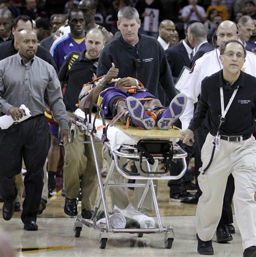 New Orleans Hornets' Chris Paul lies on the court in the second half of an NBA basketball game against the Cleveland Cavaliers in Cleveland on Sunday, March 6, 2011.  Paul was taken off the court on a stretcher. (AP Photo/Amy Sancetta)