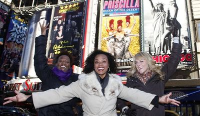 """In this Jan. 24, 2011 photo, from left, Anastacia McCleskey, Jacqueline B. Arnold and Ashley Spencer from the musical """"Priscilla Queen of the Desert"""" laugh as they pose together in front of a new billboard featuring their likenesses above the Palace Theater in New York's Times Square. (AP Photo/Jason DeCrow, file)"""