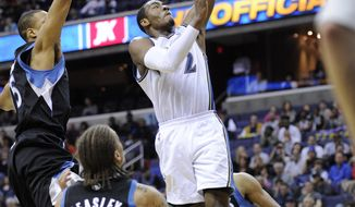 Washington Wizards point guard John Wall (2) goes to the basket against Minnesota Timberwolves' Anthony Randolph, left, and Michael Beasley (8) during the second half of an NBA basketball game, Saturday, March 5, 2011, in Washington. The Wizards won 103-96. (AP Photo/Nick Wass)